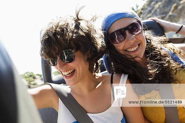Women smiling together in convertible