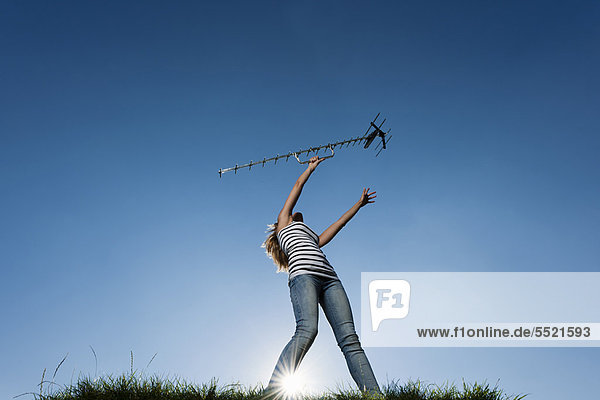 Frau hält Antenne im Freien hoch