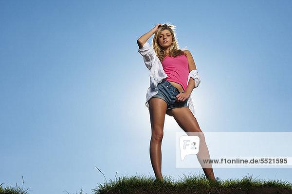 Frau posiert auf einem grasbewachsenen Hügel
