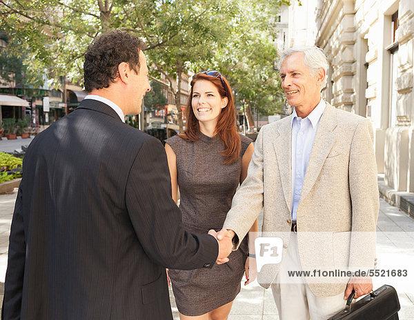 Geschäftsleute beim Händeschütteln im Freien