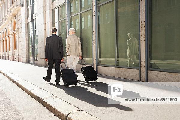 Geschäftsleute  die Gepäck ins Freie rollen.
