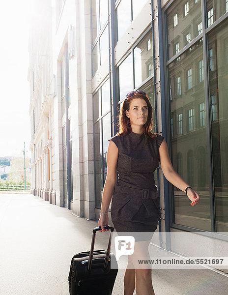 Geschäftsfrau beim Gepäckrollen im Freien