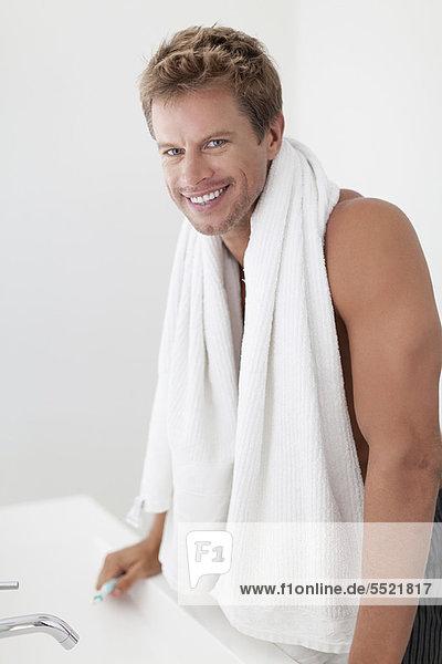 Lächelnder Mann mit Handtuch im Bad