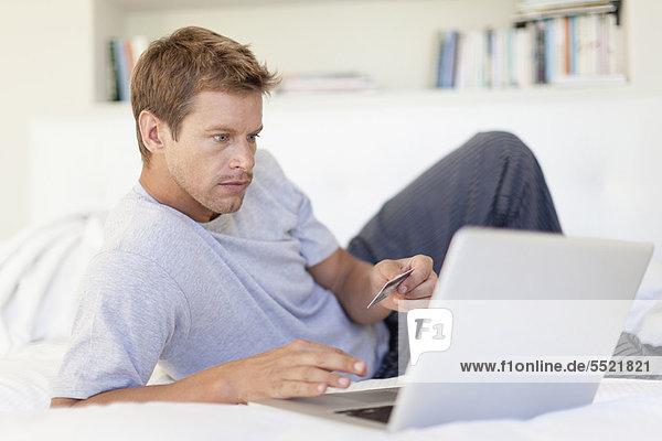 Mann online einkaufen mit Laptop