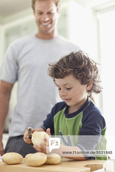 Junge schält Kartoffeln in der Küche