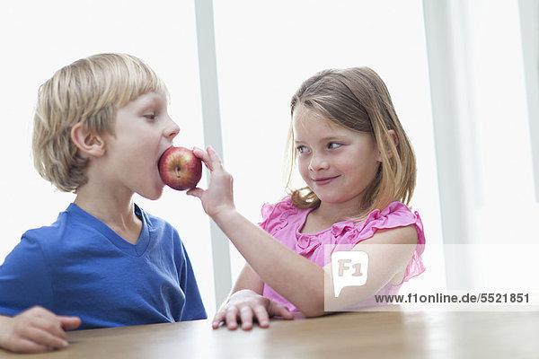 Kinder essen Apfel in der Küche