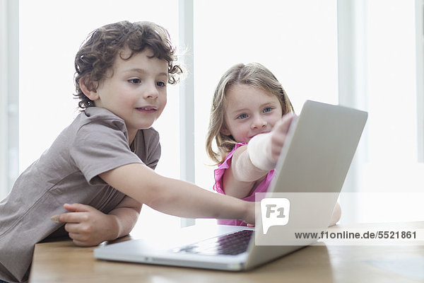 Smiling children using laptop together