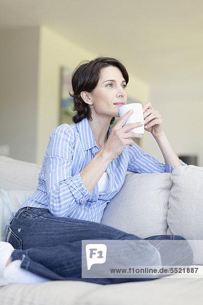 Frau trinkt eine Tasse Kaffee auf der Couch