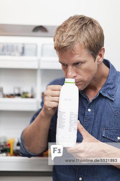 Mann riecht Milchkännchen für Frische