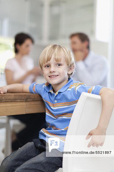 Lächelnder Junge am Tisch sitzend