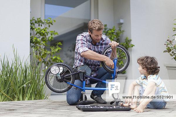 Vater hilft Sohn Fahrrad reparieren