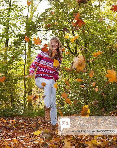 Frau spielt im Herbstlaub Frau spielt im Herbstlaub