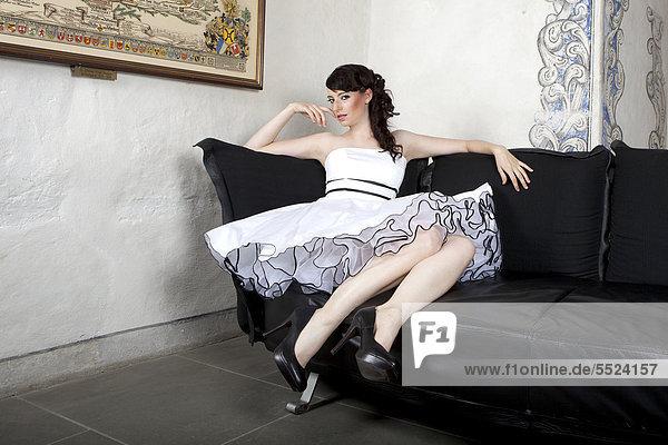 Junge Frau mit weißem Kleid auf Sofa