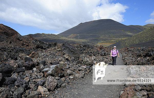Frau mit Hund beim Wandern auf La Palma  hinten Vulkan San Antonio  Kanaren  Kanarische Inseln  Spanien  Europa  ÖffentlicherGrund