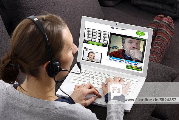 Junge Frau sitzt am Laptop und telefoniert über das Internet  per Webcam wird das Livebild beider Teilnehmer übertragen