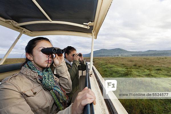 Zwei Mädchen  ca. 13 und 18 Jahre  suchen durch ein Fernglas Tiere  Lake Nakuru Nationalpark  Kenia  Ostafrika  Afrika  ÖffentlicherGrund