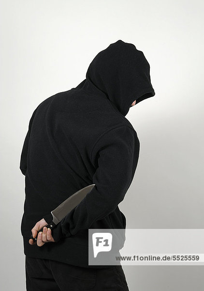 Man with a black hooded shirt and a knife behind his back