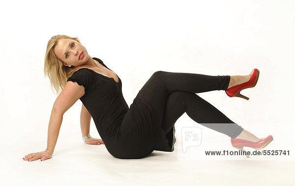 Junge Frau in schwarzem Minikleid und roten Highheels
