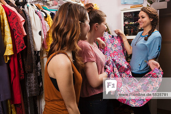Junge Frauen beim Anblick von Kleidern im Bekleidungsgeschäft