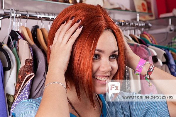 Junge Frau beim Anprobieren der Perücke im Bekleidungsgeschäft  lächelnd