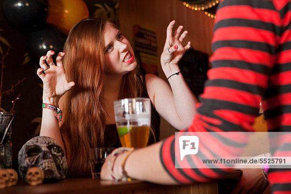 Junge Frau zieht Gesichter bei Freund in der Bar