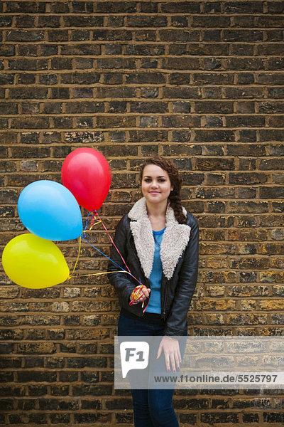Young Woman holding bunten Luftballons gegen Wand