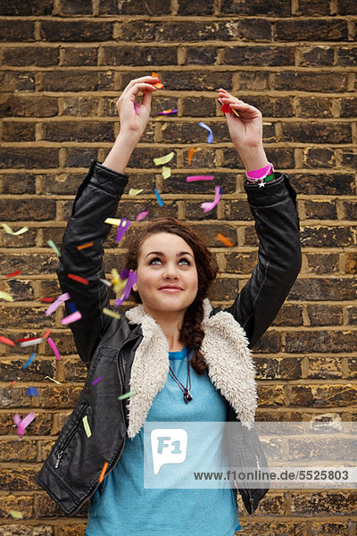 Junge Frau fallen bunte Konfetti gegen Wand