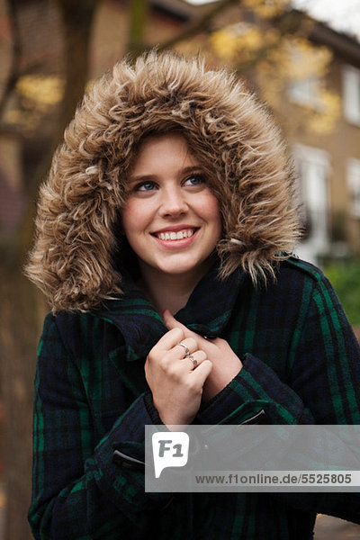 Young woman in furry hood smiling