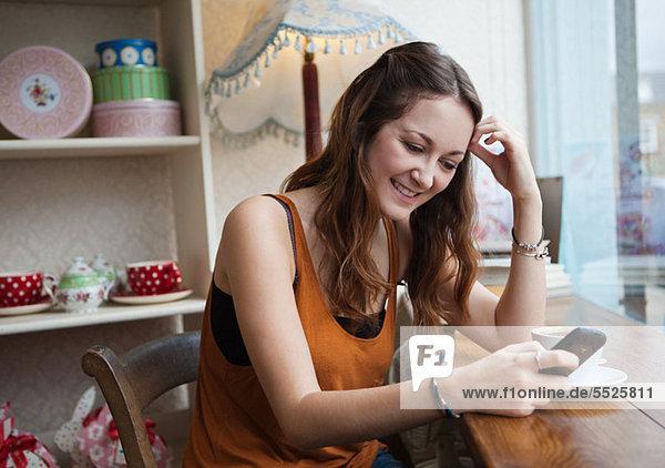 Junge Frau im Cafe mit Handy