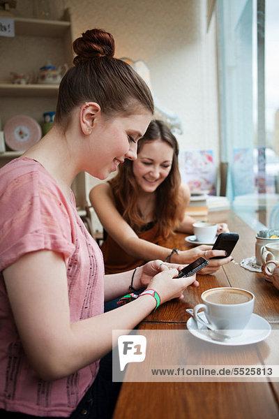 Junge Frauen im Café mit Handys