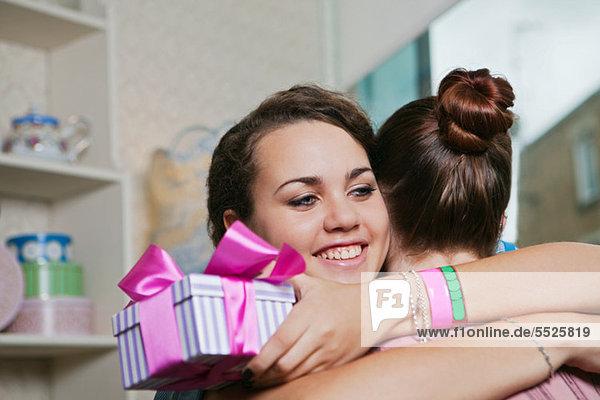 Junge Frauen mit Geburtstagsgeschenk und Umarmung