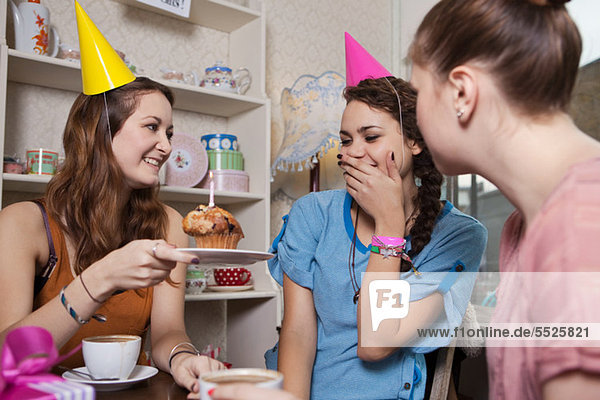 Young women celebrating friend's birthday in cafe