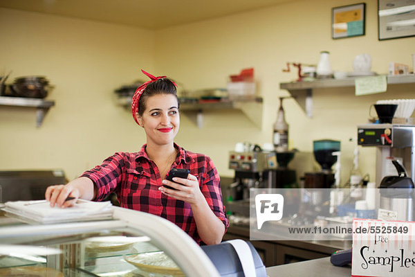 Young Woman holding Cellphone in Bäckerei