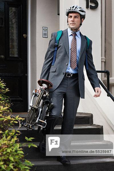 Mitte Erwachsenen Geschäftsmann Durchführung Falt Fahrrad Treppe hinunter
