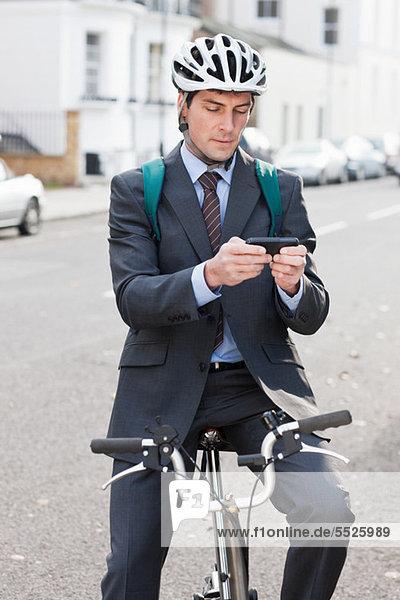 Mittlerer erwachsener Geschäftsmann  der mit dem Handy auf dem Fahrrad textet