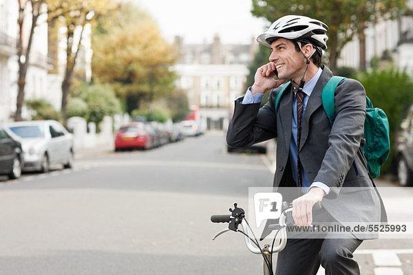 Mittlerer erwachsener Geschäftsmann mit Handy auf dem Fahrrad