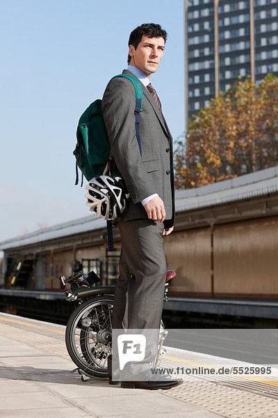 Mitte Erwachsenen Geschäftsmann Durchführung Falt Fahrrad am Bahnsteig