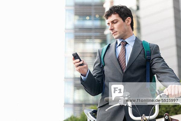 Mittlerer Erwachsener Geschäftsmann mit Fahrrad über Handy