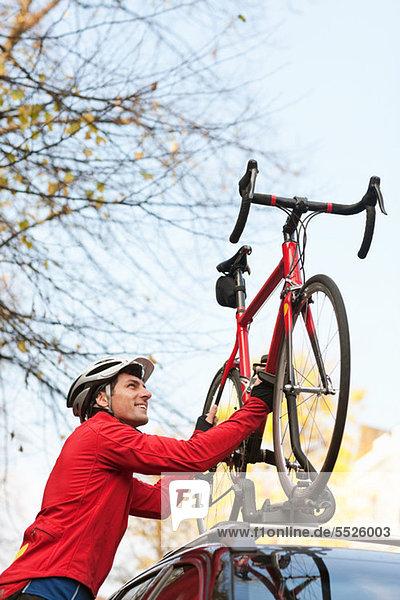Mitte erwachsenen Mann heben Fahrrad auf Auto-Dachgepäckträger