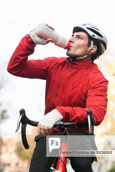 Mittlerer Erwachsener Mann  der auf dem Fahrrad trinkt