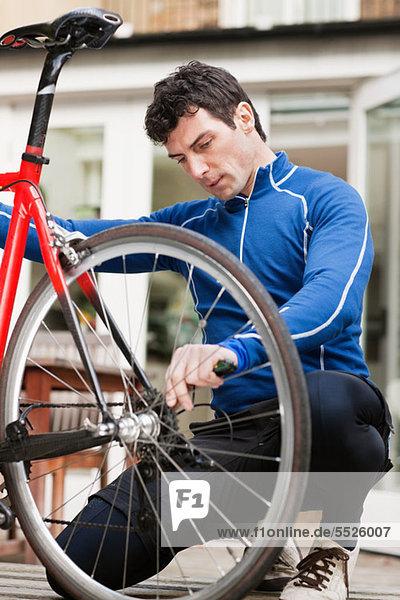Mittlerer Erwachsener Mann  der das Fahrradrad einstellt