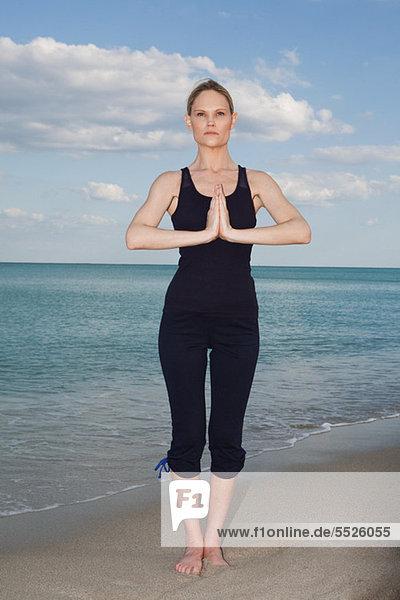 Frau Strand Mittelpunkt Yoga Erwachsener Pose