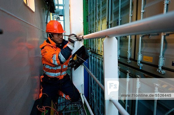 An Indonesian seaman or sailor on the container-vessel MV Flintercape  during a journey from Rotterdam  Netherlands  to Sundsvall  Sweden. The man is an ´Able Seaman´  who generally works on deck. He is now repairing the railing between wheel-house and container-deck  which has been damages during the loading of new containers.