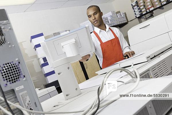 Man operating printing machine at press