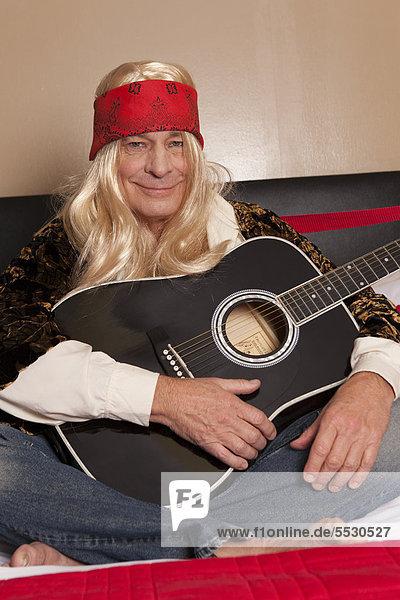Smiling senior guitarist sitting with legs crossed