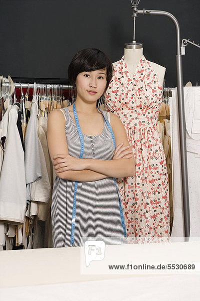 Young fashion designer with arms crossed standing next to a mannequin