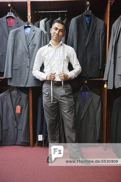 Portrait of young Man posiert mit Anzüge hängen im Hintergrund