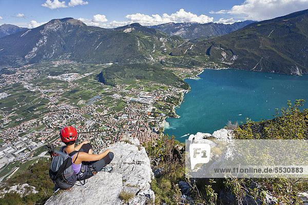 Kletterin am Klettersteig Via dell Amicizia  mit Blick auf Gardasee und Riva  Trentino  Italien  Europa