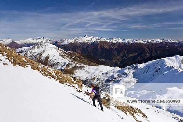 Wanderin beim Aufstieg im Schnee zur Röthenspitz oberhalb vom Penser Joch  hinten das Gebirge des Pfitschertals mit dem Hochfeiler  Sarntal  Südtirol  Italien  Europa