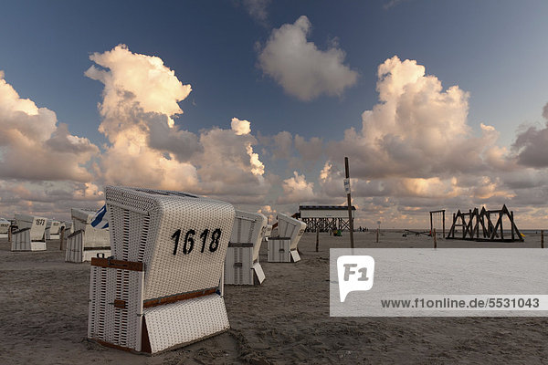 Roofed wicker beach chairs on the beach of Sankt Peter-Ording at sunset  North Friesland district  Schleswig-Holstein  Germany  Europe